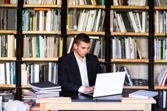 Muchacho del estudiante que trabaja en un ordenador portátil en la biblioteca Imagen de archivo libre de regalías