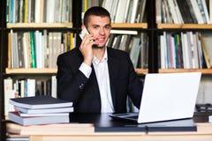 Muchacho del estudiante que trabaja en un ordenador portátil en la biblioteca Fotos de archivo libres de regalías