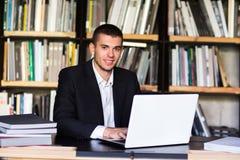 Muchacho del estudiante que trabaja en un ordenador portátil en la biblioteca Imágenes de archivo libres de regalías