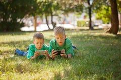 Muchacho del hermano que juega al juego en el móvil junto que miente en hierba en día soleado del parque imagenes de archivo