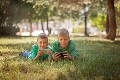 Muchacho del hermano que juega al juego en el móvil junto que miente en hierba en día soleado del parque foto de archivo