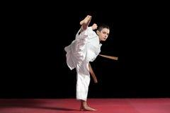 Muchacho del karate en la lucha blanca del kimono aislado en fondo negro Fotografía de archivo libre de regalías