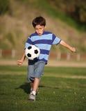 Muchacho del Latino que juega con el balón de fútbol fotos de archivo