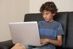 Muchacho del Latino que se sienta en el sofá con el ordenador portátil Foto de archivo