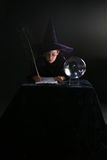 Muchacho del mago que escribe un encanto Fotos de archivo libres de regalías