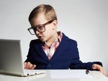 Muchacho del negocio niño divertido en vidrios que escribe la pluma pequeño jefe en oficina Foto de archivo libre de regalías
