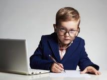 Muchacho del negocio niño divertido en vidrios que escribe la pluma pequeño jefe en oficina Fotos de archivo