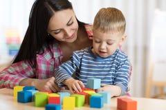 Muchacho del niño así como la madre que juega los juguetes imágenes de archivo libres de regalías