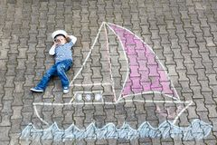Muchacho del niño como pirata en la pintura de la imagen de la nave o del sailingboat con tizas coloridas en el asfalto Imagenes de archivo