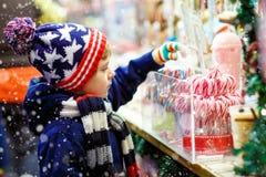 Muchacho del niño con el soporte del bastón de caramelo en mercado de la Navidad Fotografía de archivo
