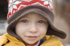 Muchacho del niño con el trineo largo del knit en nieve Fotos de archivo