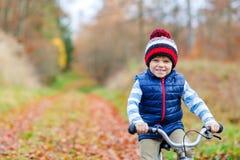 Muchacho del niño con la bicicleta en bosque del otoño Imágenes de archivo libres de regalías