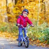 Muchacho del niño con la bicicleta en bosque del otoño Foto de archivo libre de regalías