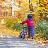 Muchacho del niño con la bicicleta en bosque del otoño Fotografía de archivo