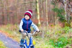 Muchacho del niño con la bicicleta en bosque del otoño Foto de archivo