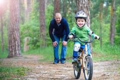 Muchacho del niño de 3 años y su padre en bosque del otoño con una bicicleta Hijo de enseñanza del papá Hombre feliz sobre éxito  Foto de archivo
