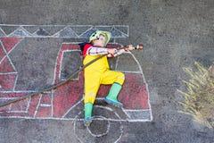 Muchacho del niño de cuatro años que se divierten con la imagen del coche de bomberos Imagen de archivo
