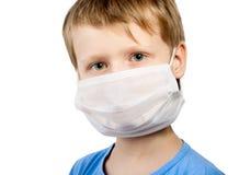 Muchacho del niño de la enfermedad de la gripe en máscara quirúrgica Imagen de archivo libre de regalías