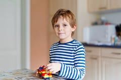Muchacho del niño de la escuela que juega con las porciones de pequeños bloques coloridos del plástico Imagen de archivo