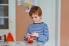 Muchacho del niño de la escuela que juega con las porciones de pequeños bloques coloridos del plástico Fotografía de archivo