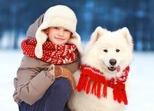 Muchacho del niño de la Navidad del retrato que camina con el perro blanco del samoyedo en invierno Imagen de archivo