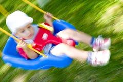 Muchacho del niño en el oscilación Imágenes de archivo libres de regalías