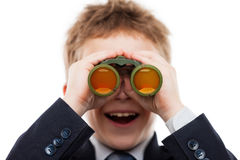 Muchacho del niño en el traje de negocios que sostiene la lente de los prismáticos que busca d Imagen de archivo