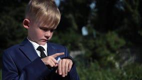 Muchacho del niño en reloj elegante del uso del traje de negocios en la calle Ciérrese encima de tiro
