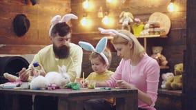 Muchacho del niño hermoso que pinta los huevos de Pascua Familia feliz que se prepara para Pascua Oídos del conejito del muchacho almacen de video