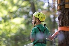 Muchacho del niño joven en arnés de seguridad y casco atado con la carabina al cable en manera de la cuerda en parque fotos de archivo libres de regalías