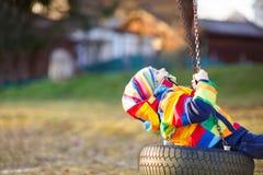 Muchacho del niño que balancea en patio al aire libre Imagen de archivo
