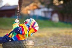 Muchacho del niño que balancea en patio al aire libre Fotos de archivo