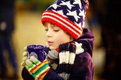 Muchacho del niño que bebe el chocolate caliente en mercado de la Navidad foto de archivo