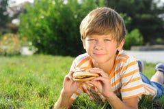 Muchacho del niño que come la hamburguesa al aire libre Fotos de archivo