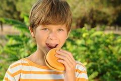 Muchacho del niño que come la hamburguesa al aire libre Fotografía de archivo libre de regalías