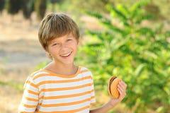 Muchacho del niño que come la hamburguesa al aire libre Imagenes de archivo