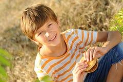 Muchacho del niño que come la hamburguesa al aire libre Foto de archivo libre de regalías