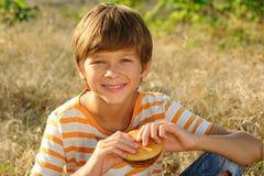 Muchacho del niño que come la hamburguesa al aire libre Imagen de archivo libre de regalías