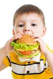 Muchacho del niño que come la hamburguesa deliciosa aislada Fotos de archivo