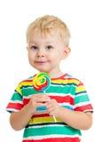 Muchacho del niño que come la piruleta aislada Imagen de archivo libre de regalías