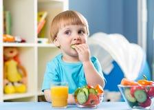 Muchacho del niño que come verduras en casa Fotos de archivo