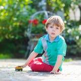 Muchacho del niño que juega con el juguete del coche, al aire libre Imagen de archivo