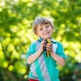 Muchacho del niño que juega con el juguete del coche, al aire libre Imagen de archivo libre de regalías