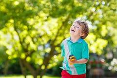 Muchacho del niño que juega con el juguete del coche, al aire libre Fotos de archivo