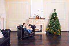 Muchacho del niño que juega con el oso suave del juguete cerca del árbol de navidad Fotos de archivo