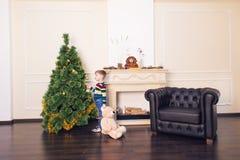 Muchacho del niño que juega con el oso suave del juguete cerca del árbol de navidad Imagen de archivo