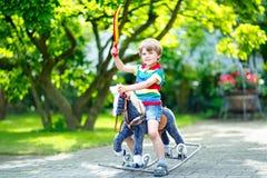Muchacho del niño que juega con su caballo mecedora del juguete en un parque del verano Foto de archivo