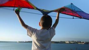 Muchacho del niño que juega con vista posterior del ala flexible del juguete Niño contra el mar del verano y el fondo del cielo C metrajes