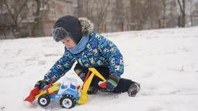 Muchacho del niño que juega en un juguete automotriz un tractor en la nieve almacen de metraje de vídeo