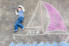Muchacho del niño que se divierte con el dibujo de la imagen de la nave con tiza Imagen de archivo libre de regalías